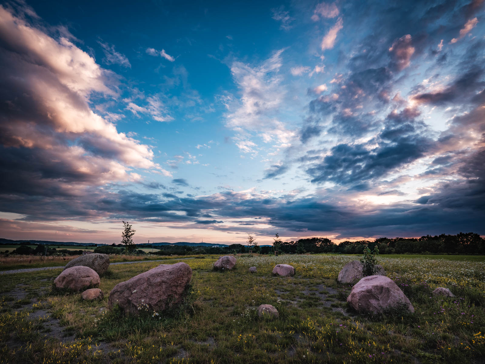 Landscape with erratic rocks at dusk in July 2020 (Bielefeld, Germany).